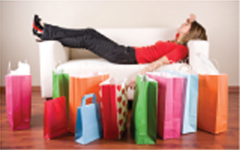 woman laying down after a long day of shopping, surrounded by bags from different stores