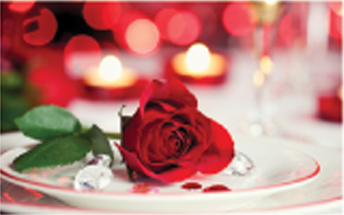 red rose on a plate with candels out of focus inteh background